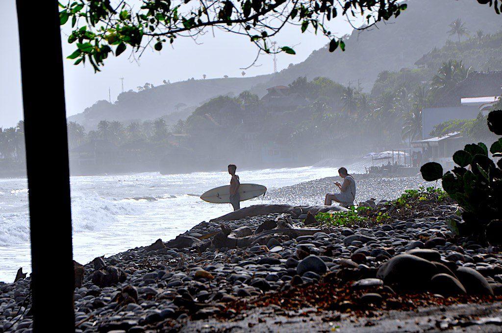 Der junge Surfer und das Meer in El Tunco