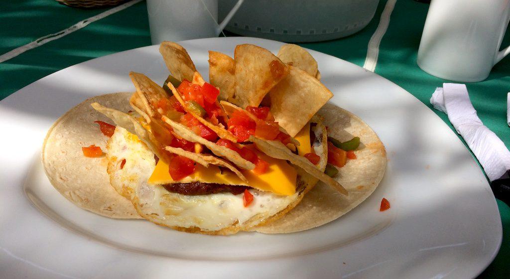 Frühstück in El Salvador, Nachos, Tomaten, Käse, Ei und Bohnenpürree auf kleinen Tortillafladen