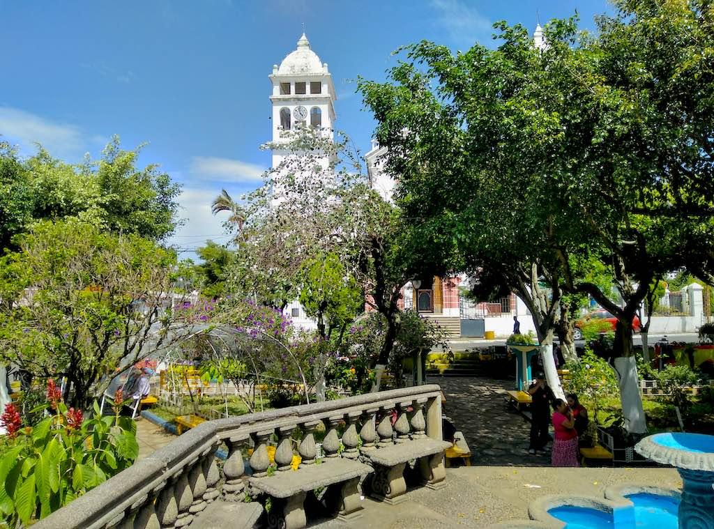 Die grüne Plaza Central in Juayúa auf der Ruta de las Flores mit der Iglesia Santa Lucia im Hintergrund.