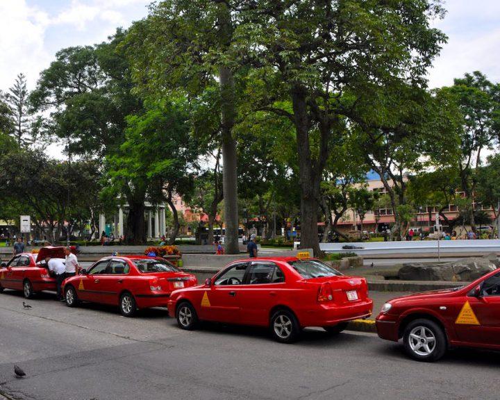 Rote Taxis warten am Parque Morazán auf Kundschaft in Costa Ricas Hauptstadt San José.
